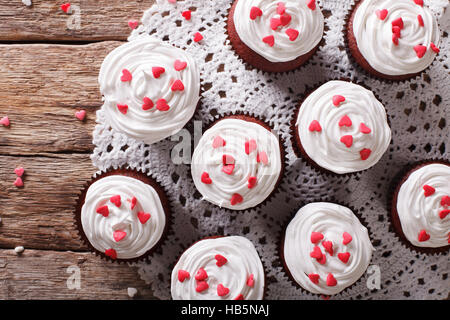 red velvet cupcakes decorated with hearts close-up on the table. horizontal view from above - Stock Photo