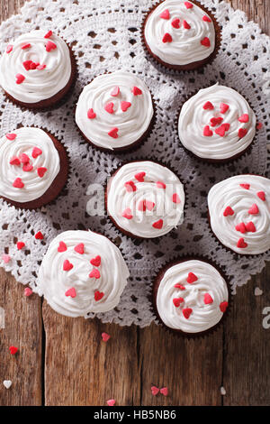 tasty red velvet cupcakes on a lacy napkin close-up on the table. vertical view from above - Stock Photo