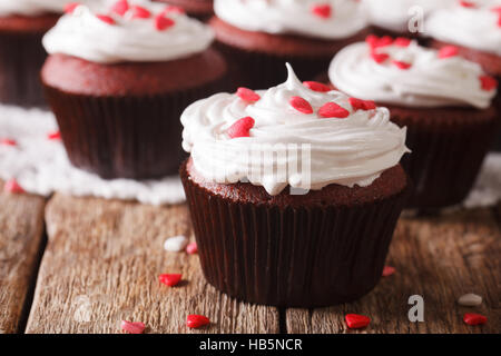 festive red velvet cupcakes decorated with hearts macro on the table. horizontal - Stock Photo
