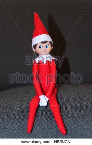 Elf on the Shelf soft children's Christmas toy seated on a couch from The Elf on the Shelf: A Christmas Tradition - Stock Photo