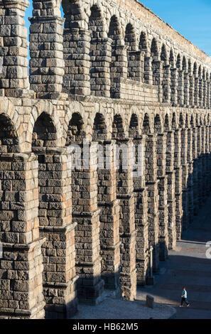 Looking along Segovia's 1st century Roman Aqueduct in the Plaza Azuguejo, Segovia, Spain - Stock Photo
