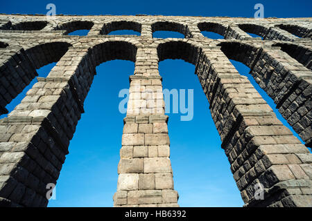Looking up at Segovia's 1st century Roman Aqueduct in the Plaza Azuguejo, Segovia, Spain - Stock Photo