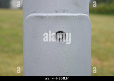 Close-up of the screw on a streetlight on a field background - Stock Photo