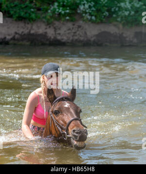 A young woman rides her horse in the River Eden at Appleby Horse Fair in Cumbria, UK - Stock Photo