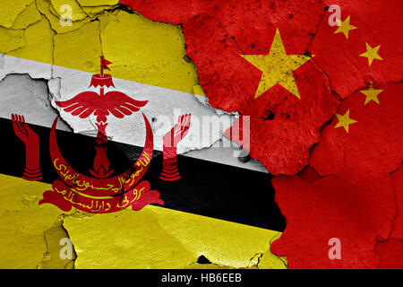 flags of Brunei and China painted on cracked wall - Stock Photo