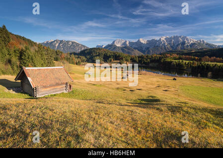Haystack above Lake Gerold and the Karwendel mountains surrounded by colorful humpy meadows and autumn forest in - Stock Photo