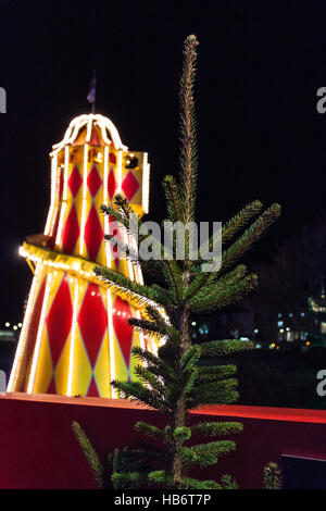 Detailed close up of bare Christmas tree, with a bright red and yellow Helter Skelter in the background. Edinburgh's - Stock Photo