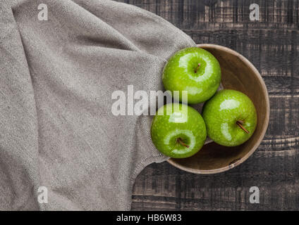 Green healthy apples in wooden bowl kitchen cloth on wooden background - Stock Photo