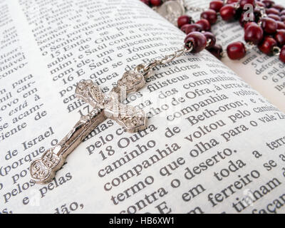 Rosary over an old holy bible written in Portuguese. Close up detail. - Stock Photo