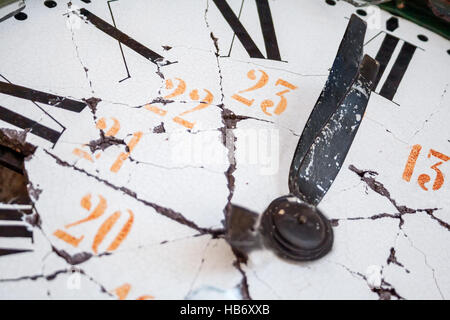 Old and damaged clock with roman numerals, marking a minute to midnight. New year eve theme. - Stock Photo
