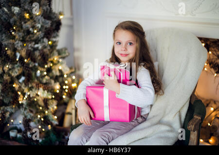Beautiful girl near Christmas tree unpacking presents sitting on a chair - Stock Photo