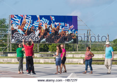 Group of tourists visiting Che Guevara memorial or plaza. Group of people standing on road in front of Pueblo billboard. - Stock Photo