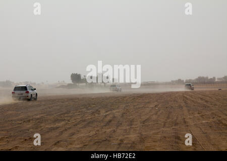 Cars driving to the safari camp after dune bashing in Dubai, UAE - Stock Photo