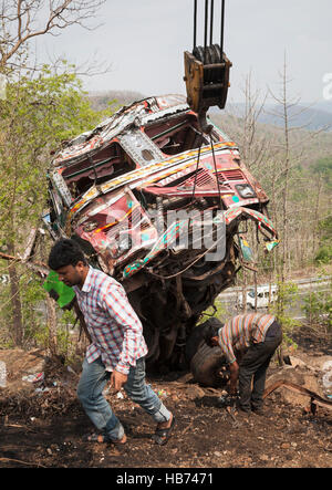 Wrecked Indian truck being recovered after crashing down a hillside. Madhya Pradesh, India - Stock Photo