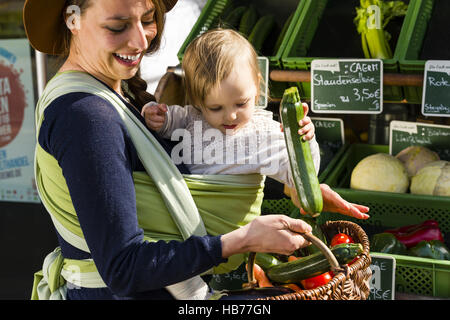 mother and child in baby sling - Stock Photo