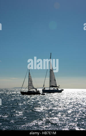 Two yachts anchored in Tenby bay prepare to set sail on a blue cloudless sky and the sun reflecting on the sea. - Stock Photo