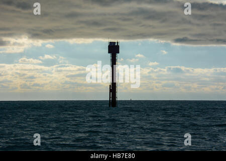 Mid channel marker post seems to be holding up the strong November sky full of clouds over the dark blue sea - Stock Photo