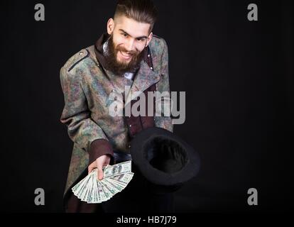 Man pulling out money from a magical hat. - Stock Photo