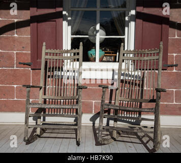 Two rocking chairs in front of an historic house. - Stock Photo
