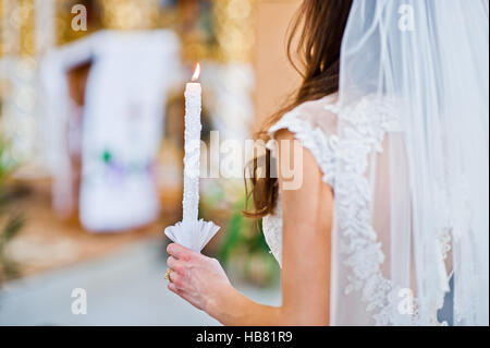 Wedding candle at hand of bride in church - Stock Photo
