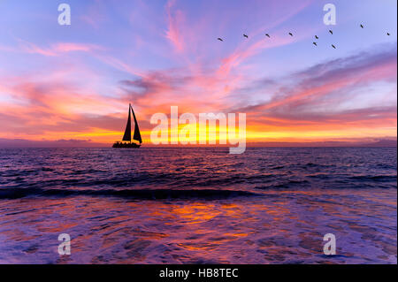 Ocean sunset sailboat silhouette is sailboat sailing along the ocean water with a colorful vivid sunset sky and - Stock Photo