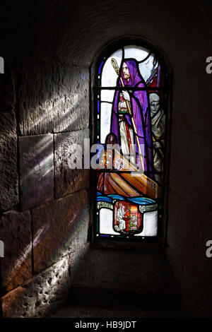 Sunlight streams through stained glass window showing Saint Columba inside Saint Margaret's Chapel, Edinburgh Castle, - Stock Photo