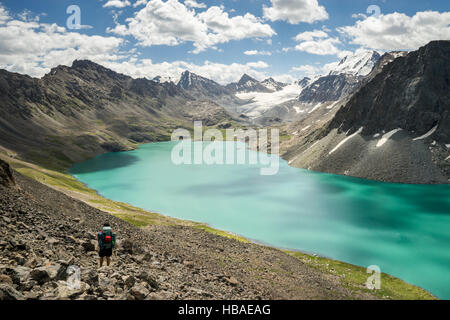 A mountaineer man stops on his trekking trail to observe the snow-capped mountains and Ala Kul Lake, Kyrgyzstan - Stock Photo
