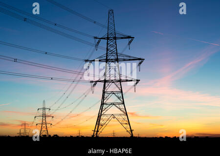 Electricity pylons silhouette against a dawn sky. UK - Stock Photo