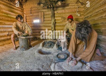 Men preparing food, life-size diorama, Carpathian Troy Archaeological Open-Air Museum in Trzcinica near Jaslo, Malopolska, - Stock Photo