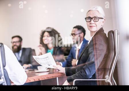 Businesswoman looking over her shoulder in board team meeting - Stock Photo