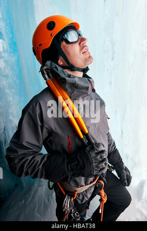Portrait of ice climber in ice cave looking up - Stock Photo