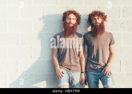 Portrait of identical adult male twins with red hair and beards against wall - Stock Photo