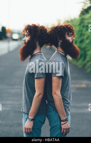 Portrait of identical adult male twins with red hair and beards back to back on sidewalk - Stock Photo