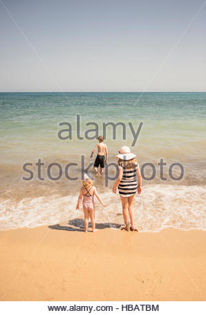 Rear view of woman with son and daughter paddling in sea, Altea, Alicante Province, Spain - Stock Photo
