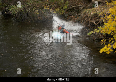 Young female kayaker splashing whilst paddling river Dee, Llangollen, North Wales - Stock Photo