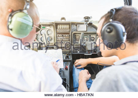 Rear view of pilot and co-pilot sitting in aircraft, talking through flight plan - Stock Photo