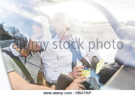 Pilot and co-pilot sitting in aircraft, talking through flight plan - Stock Photo