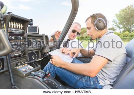 Pilot and co-pilot talking through flight plan - Stock Photo