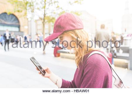 Woman in urban area using smartphone smiling, London, UK - Stock Photo