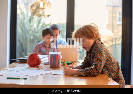 Boy colouring at dining table whilst father using laptop with brother - Stock Photo