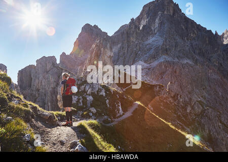 Rear view of female hiker hiking in Dolomites, Sexten, South Tyrol, Italy - Stock Photo