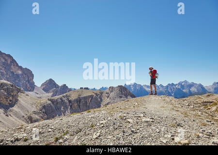 Rear view of female hiker looking out at Dolomites, Sexten, South Tyrol, Italy - Stock Photo