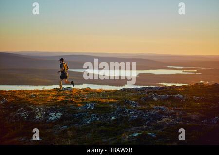 Man running on cliff top at sunset, Keimiotunturi, Lapland, Finland - Stock Photo