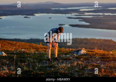 Man resting after running on cliff top at sunset, Keimiotunturi, Lapland, Finland - Stock Photo