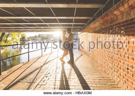 Romantic young couple under bridge on Regent's Canal, London, UK - Stock Photo