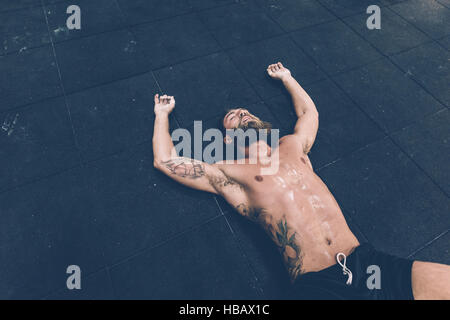 Exhausted male cross trainer lying on gym floor - Stock Photo
