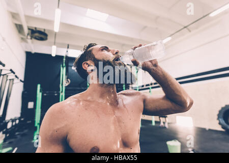 Exhausted male cross trainer drinking water in gym - Stock Photo