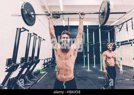 Young male cross trainer snatch lifting barbell in gym - Stock Photo