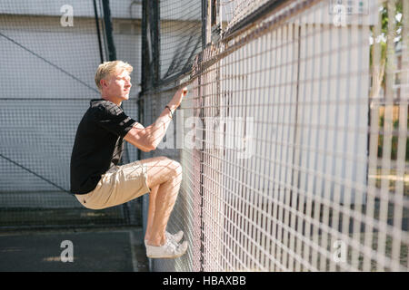 Young man climbing wire fence - Stock Photo