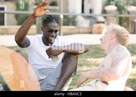 Two young men high fiving each other in park - Stock Photo